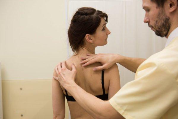 Физическое обследование, когда врач изучает искривления в позвоночнике во всех плоскостях визуально