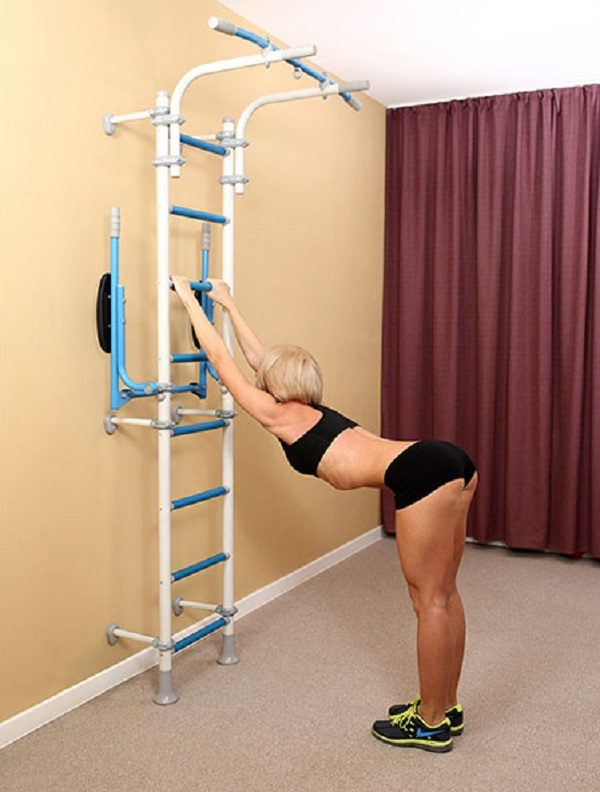 Упражнение около шведской стенки на растяжку позвоночника